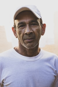 Older man in a white t shirt and white cap