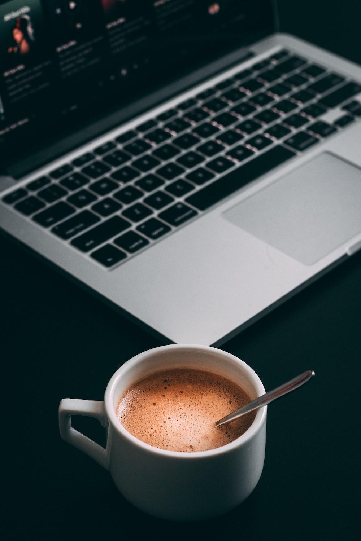 MacBook Pro near white teacup