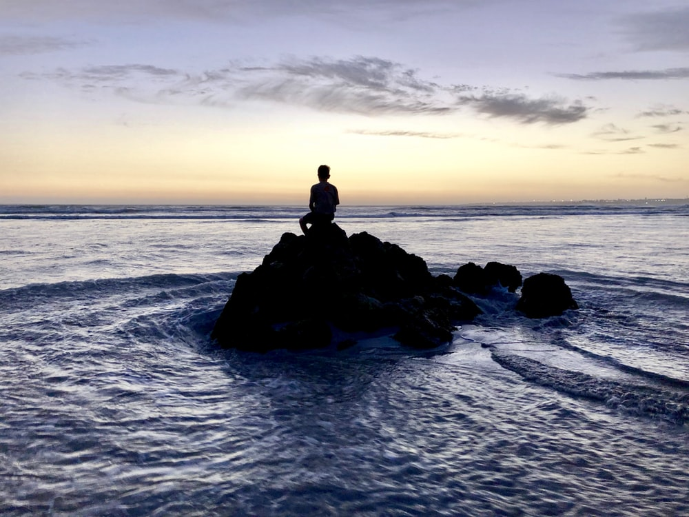 silhouette photo of person sitting on rock formation in between body of water