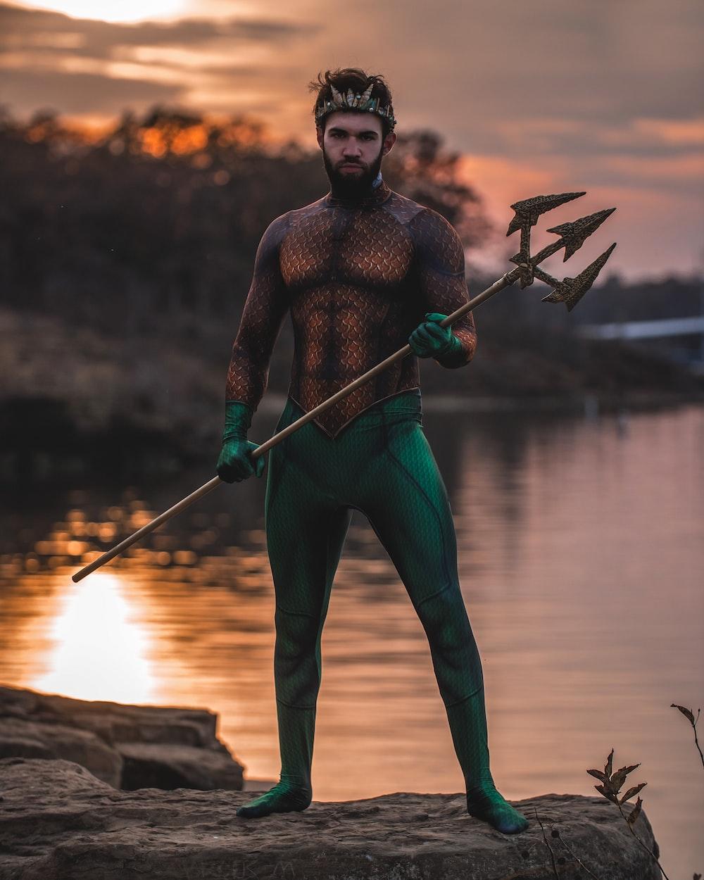 man wearing Poseidon costume standing on rock