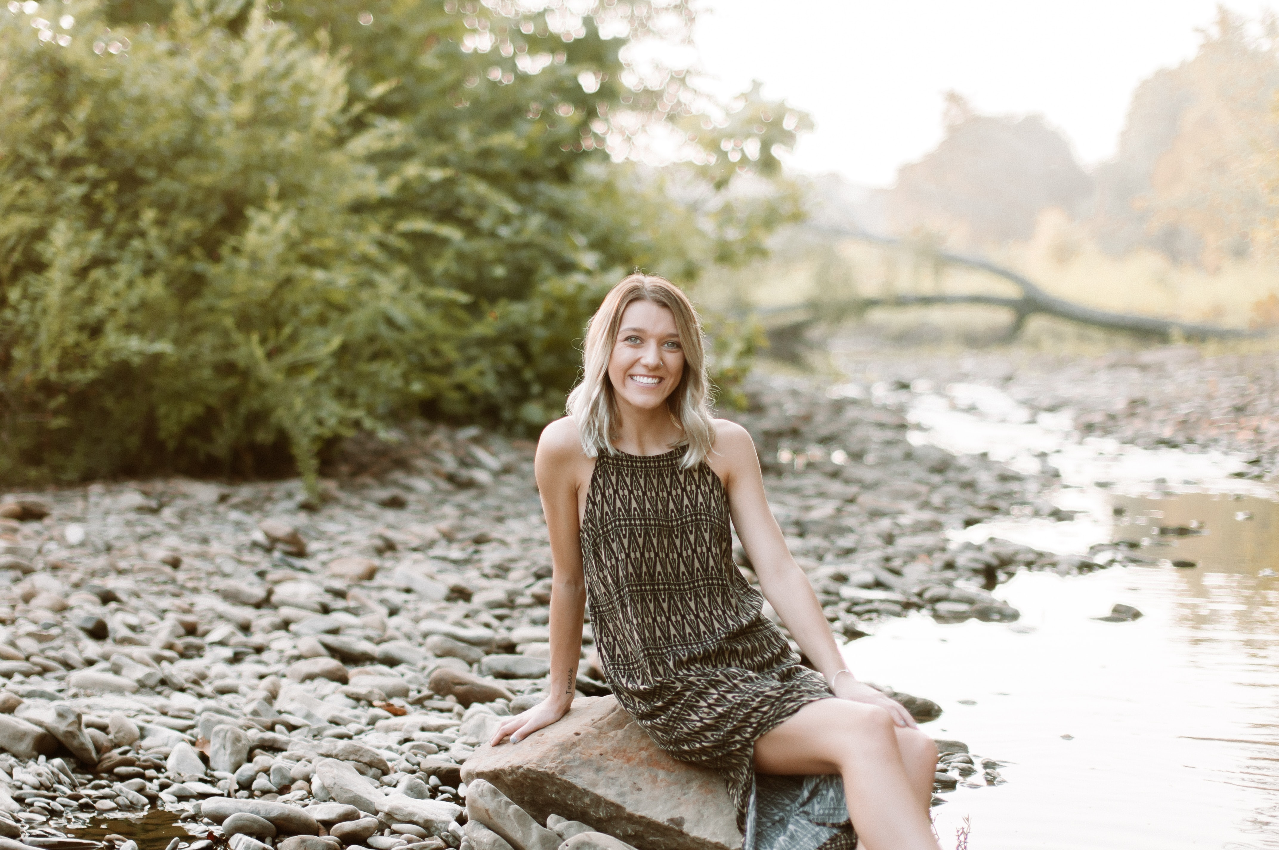 smiling woman sitting on bench beside body of water