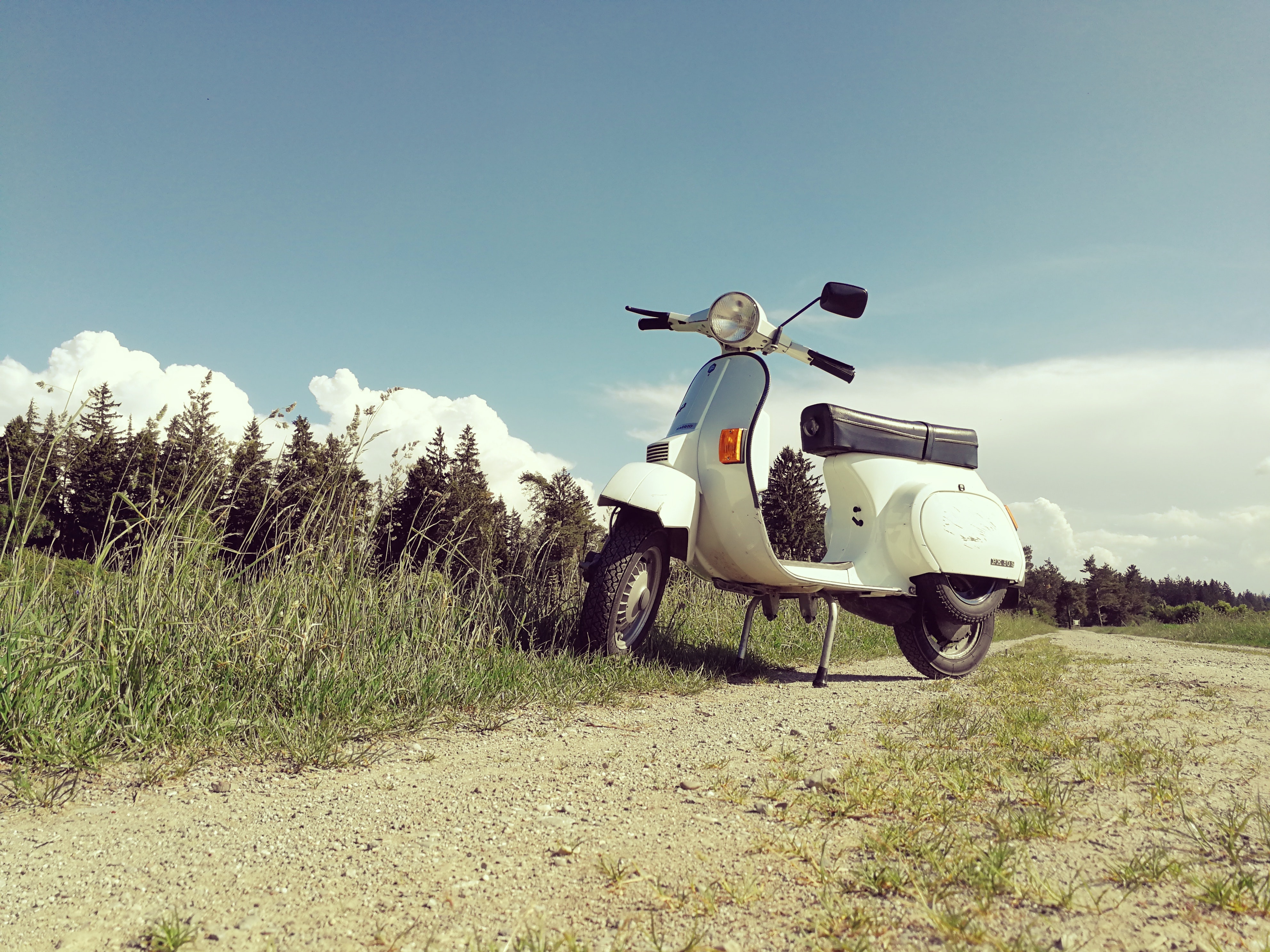 white motor scooter parked beside grass field on outdoors