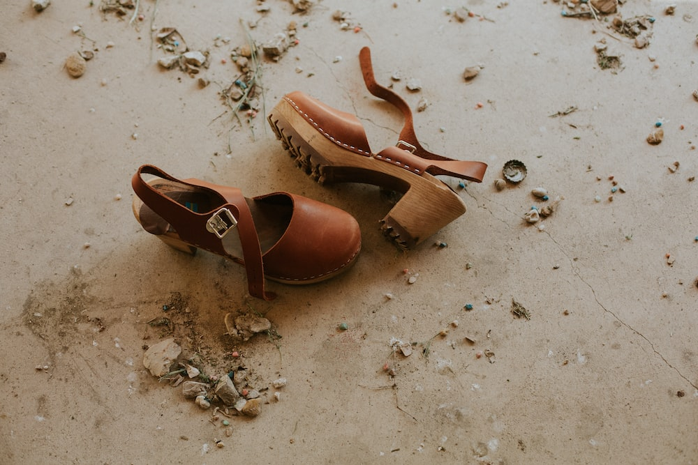 pair of brown ankle-strap sandals on floor