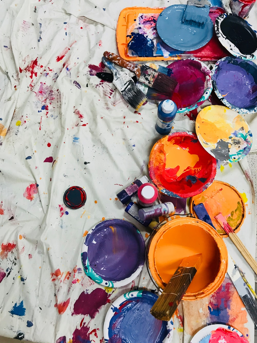 assorted-color paints and paintbrushes on white tarp