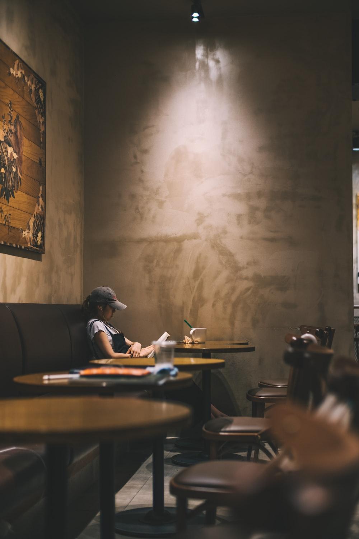woman reading book inside coffee shop