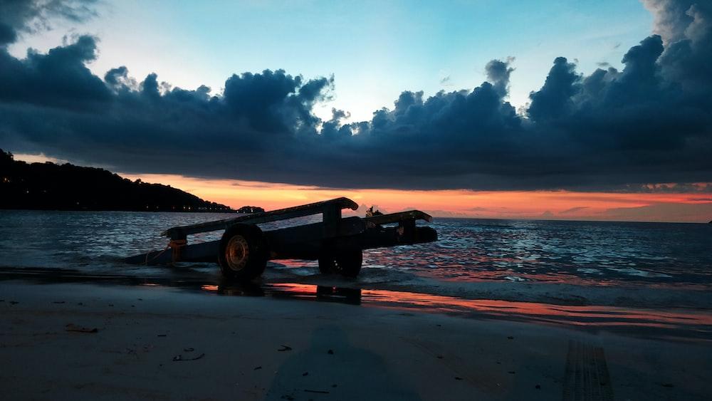 flatbed trailer left on seashore under dark cloudy sky