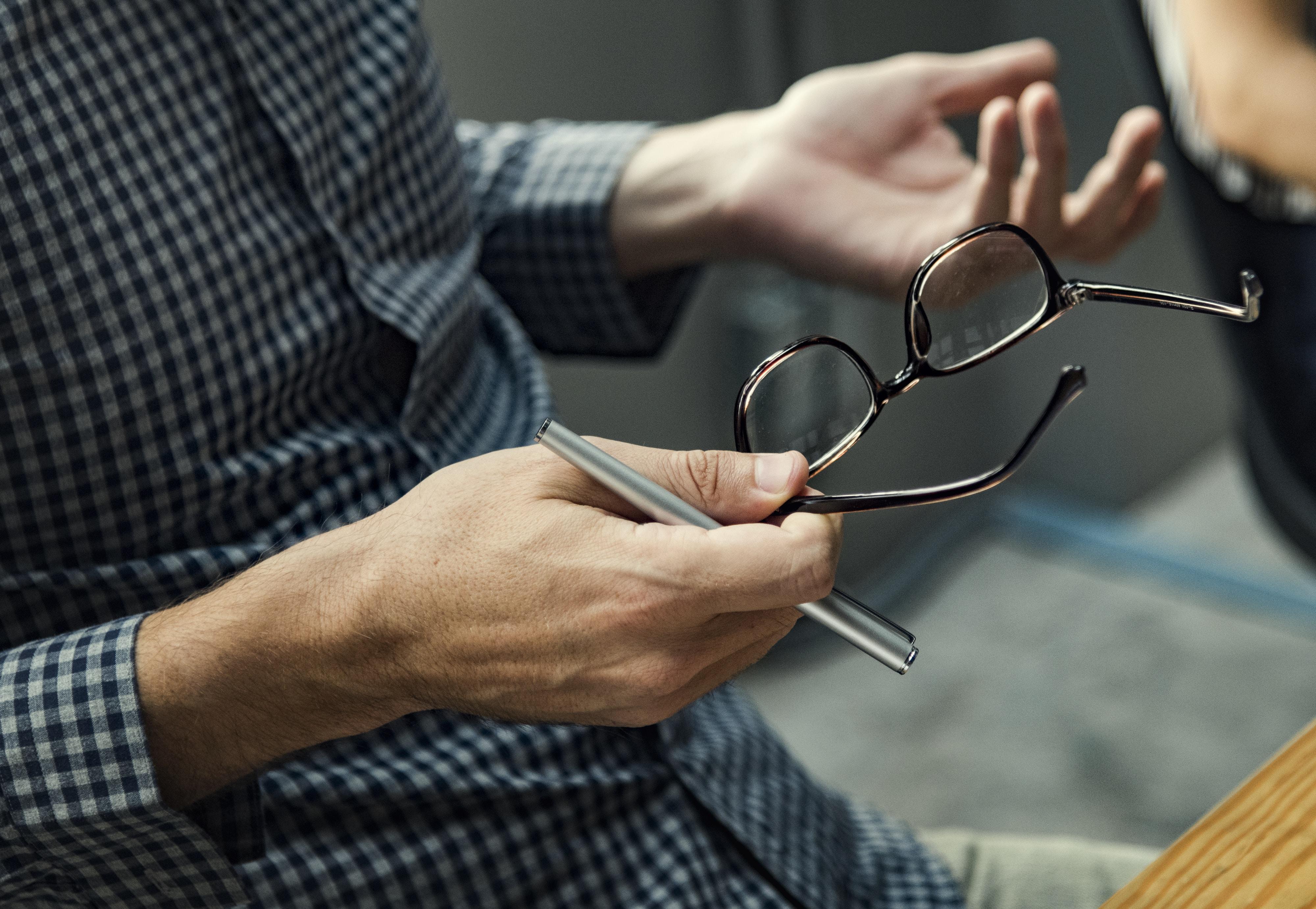 man holding his eyeglasses white sitting