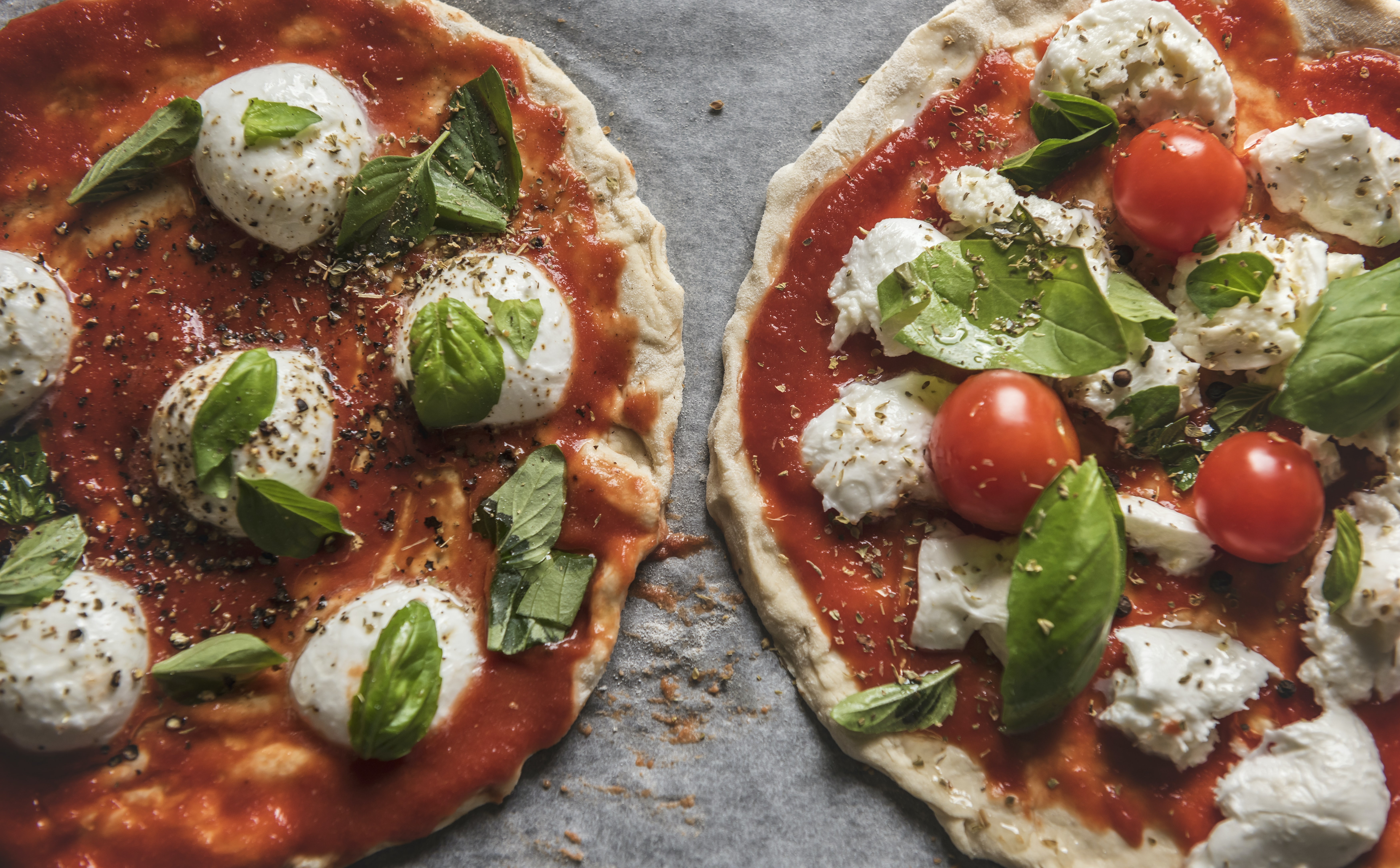 two baked pizza with tomatoes and green leaves toppings