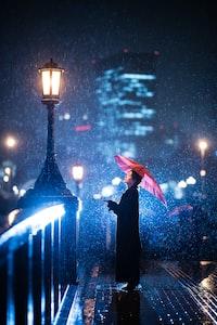 woman using umbrella standing near bridge light post