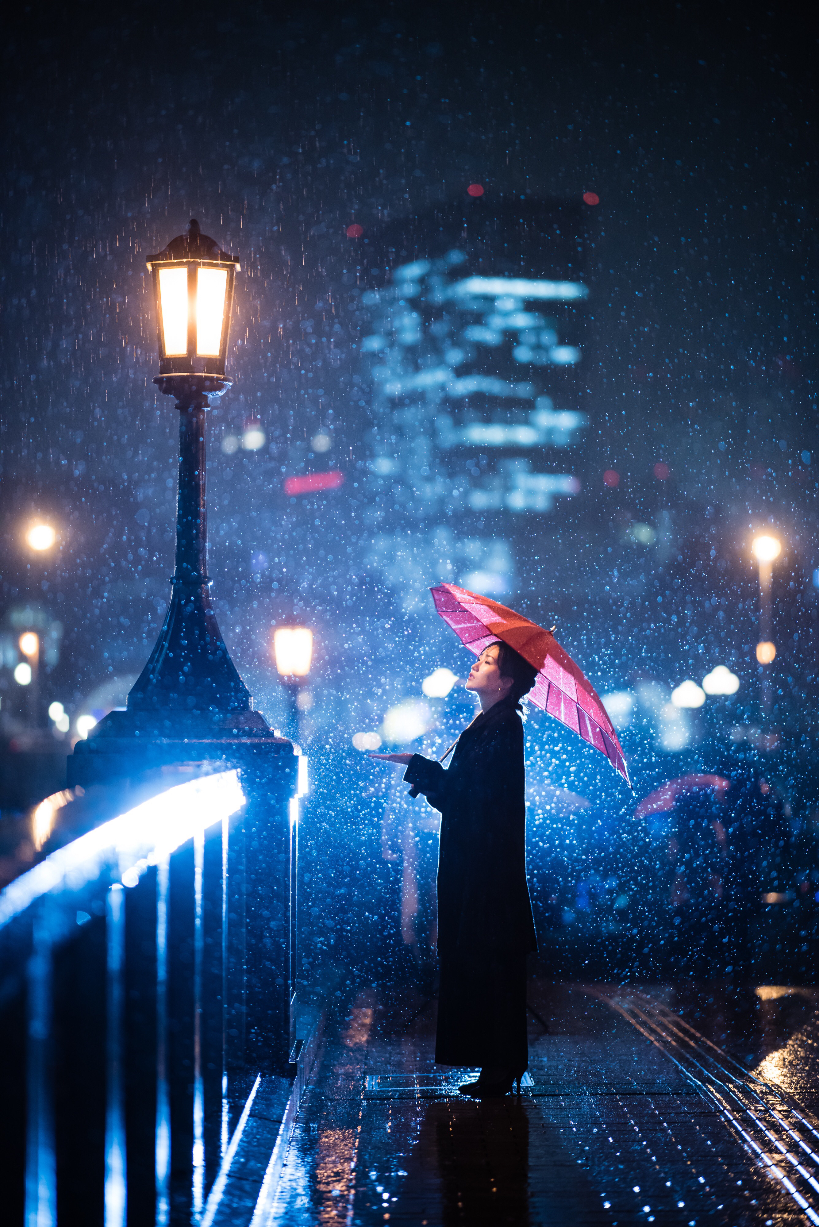 Woman Using Umbrella Standing Near Bridge Light Post
