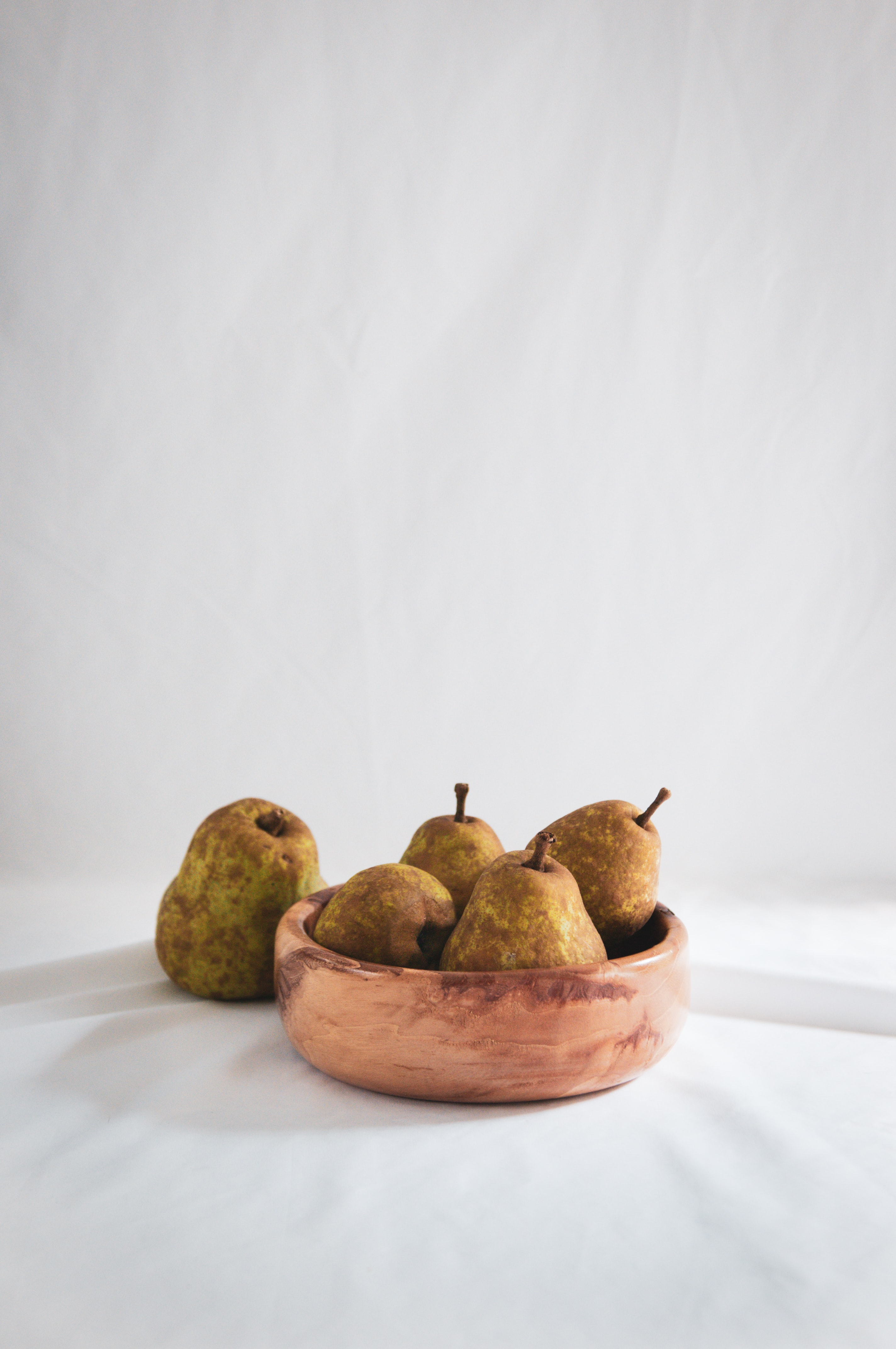 five pears fruit on brown wooden bowl