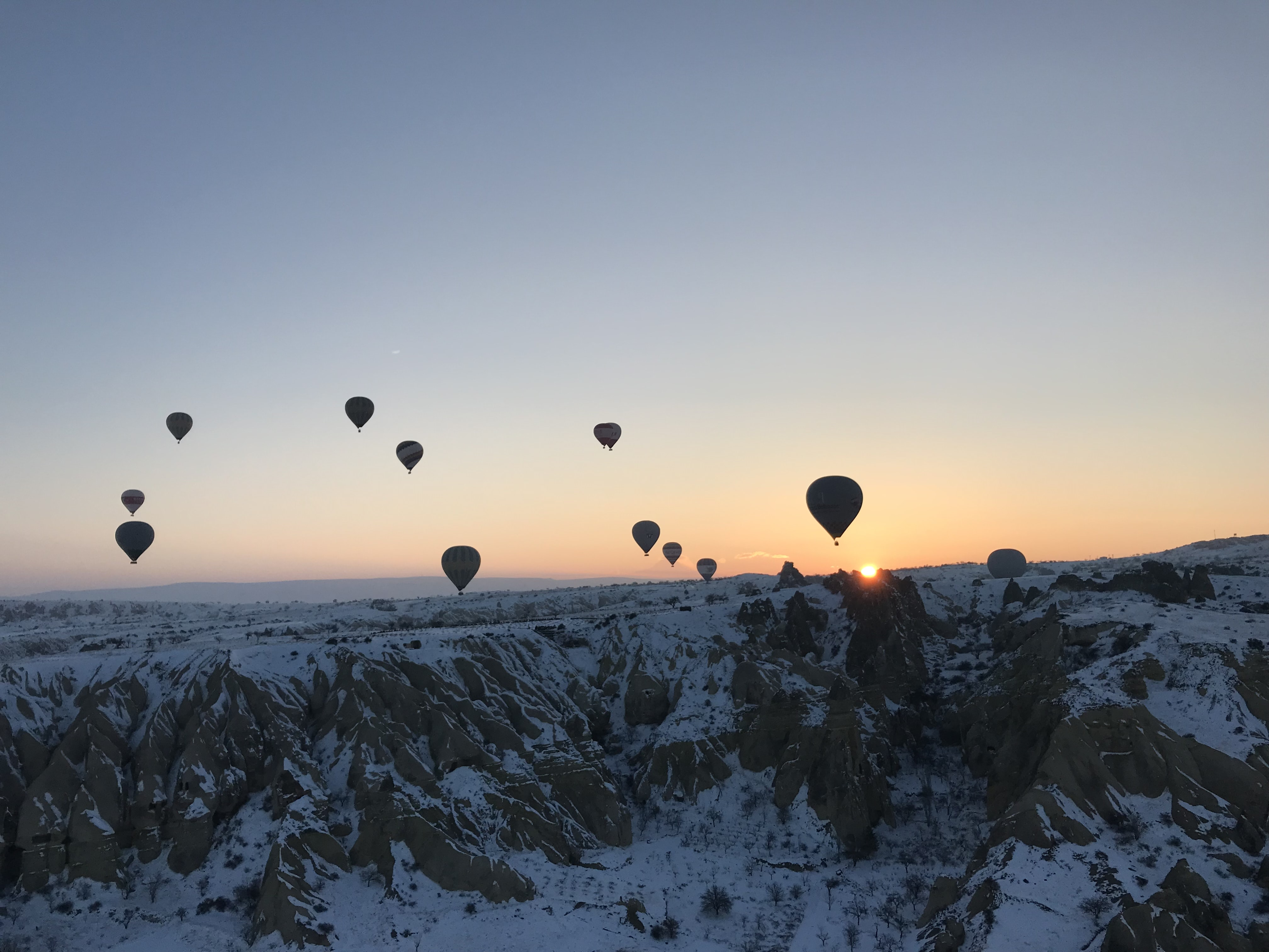 hot air balloon flying over snow capped mountain during golden hour