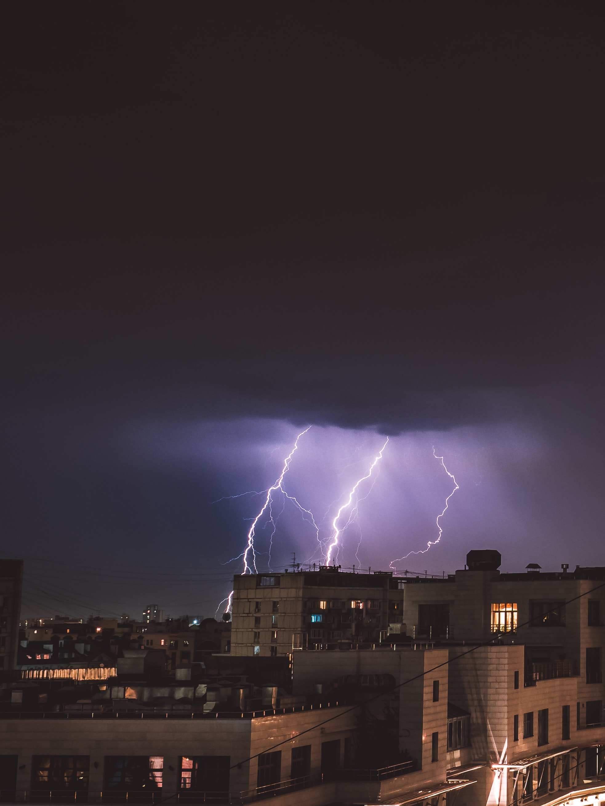 lightning over concrete buildings during nighttime