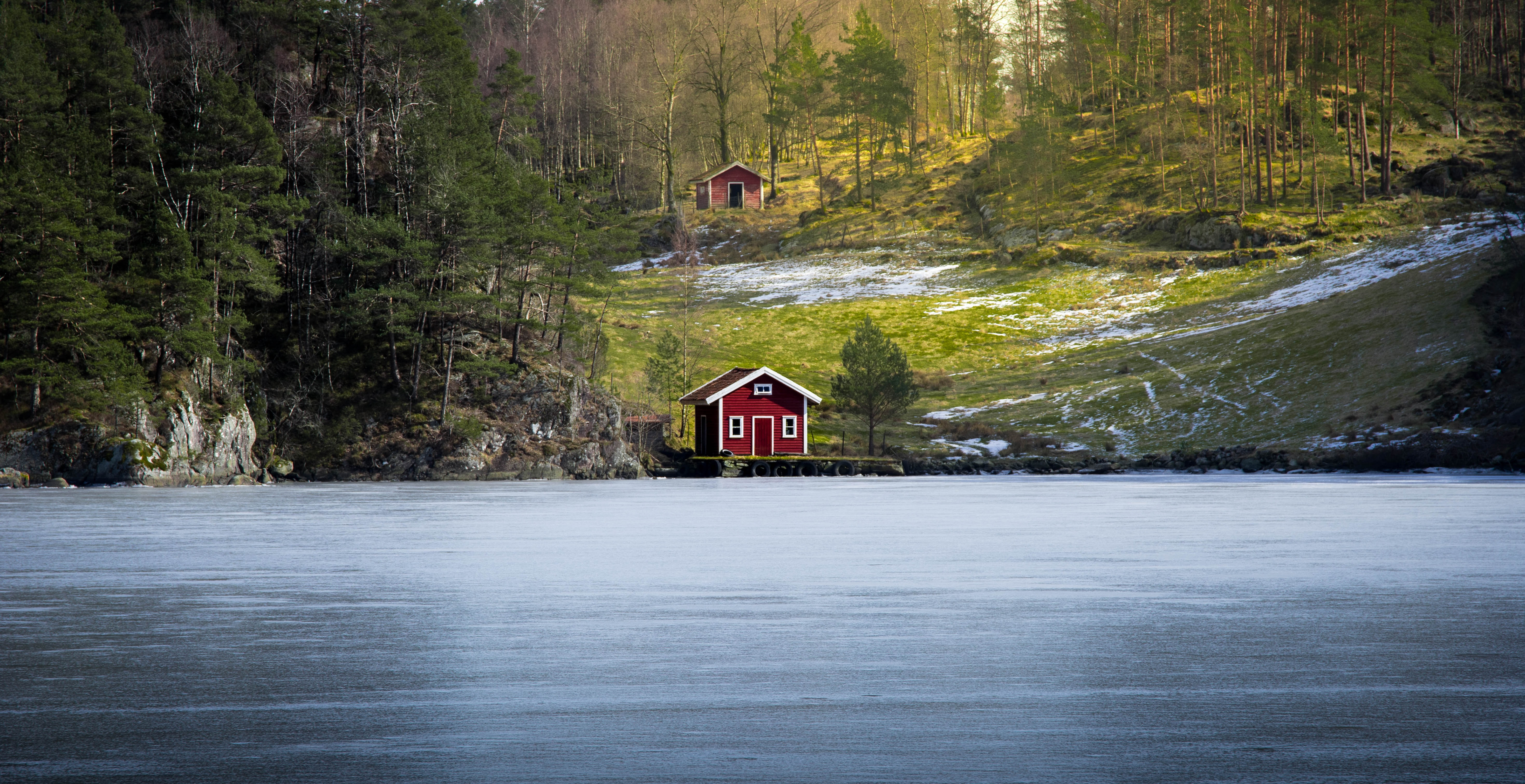 red house beside body of water surrounded by trees