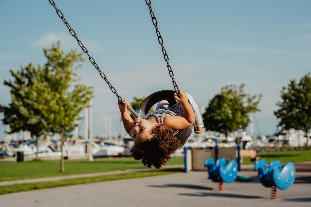 Toddler swinging at the harbor near Burlington, Ontario.