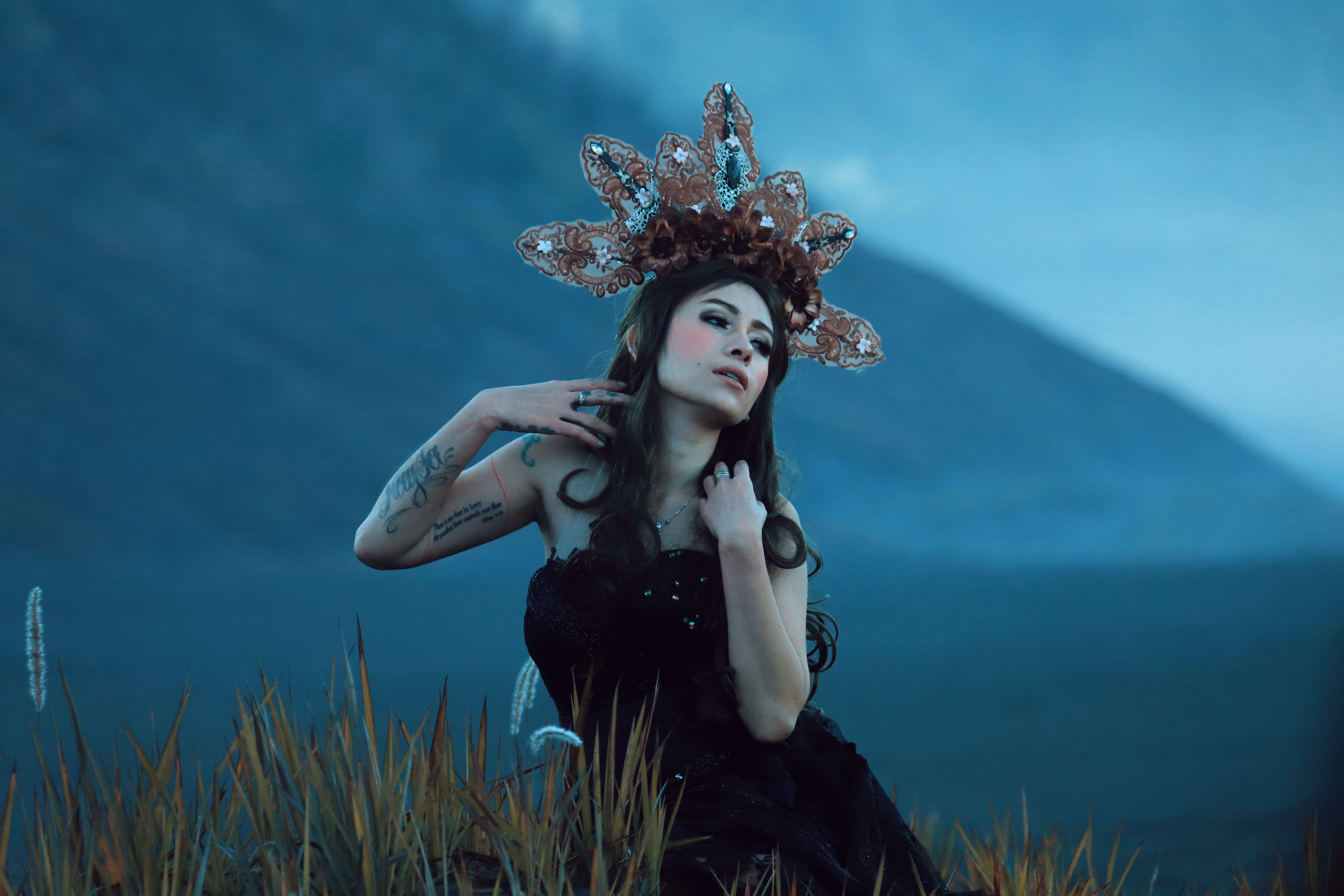 woman wearing black tube top with brown and white headdress standing in field