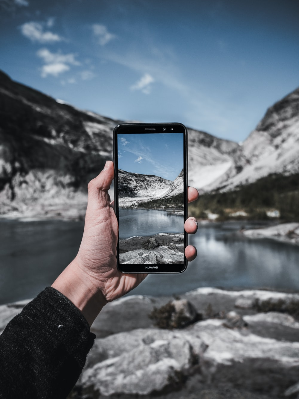 person holding black smartphone taking photo of lake during daytime