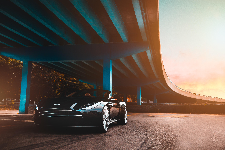 black Aston Martin convertible coupe parked beside blue concrete bridge