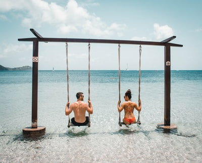 man and woman on swing on body of water saint lucia teams background