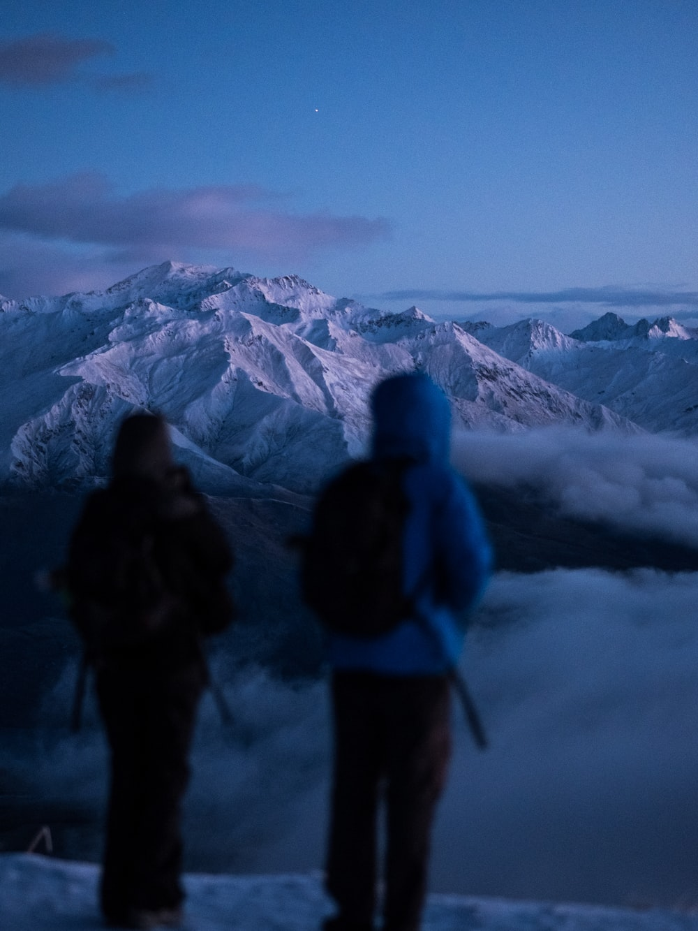 two person standing on mountain edge with fogs under blue sky