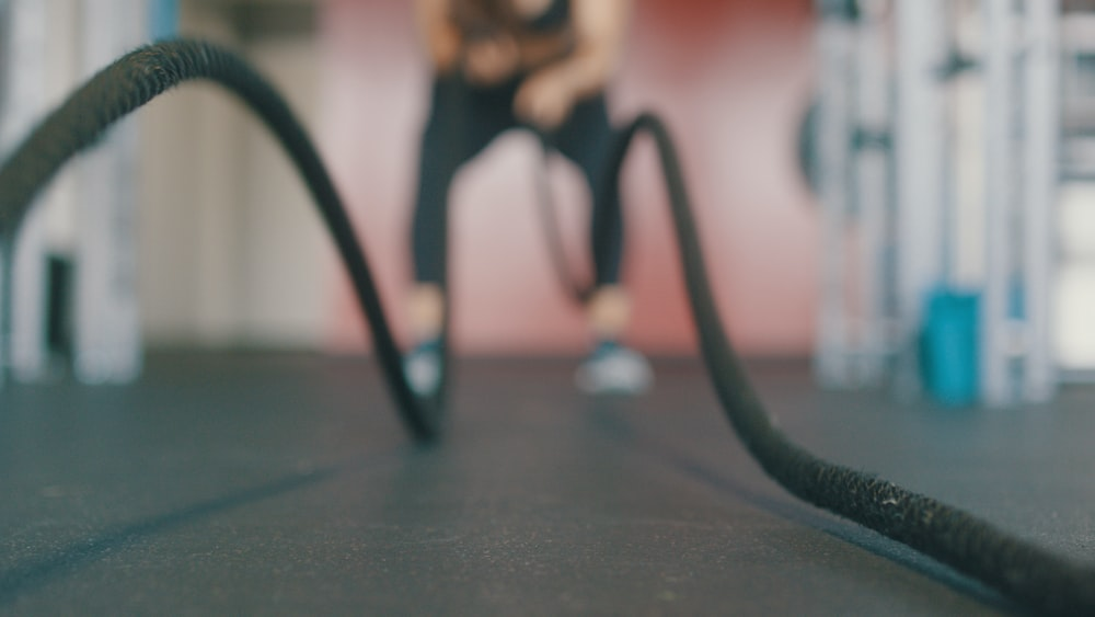 person holding black exercise rope