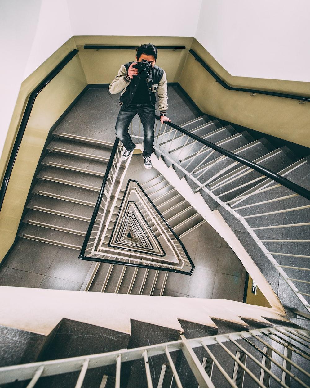 man sitting on stair rail holding DSLR camera