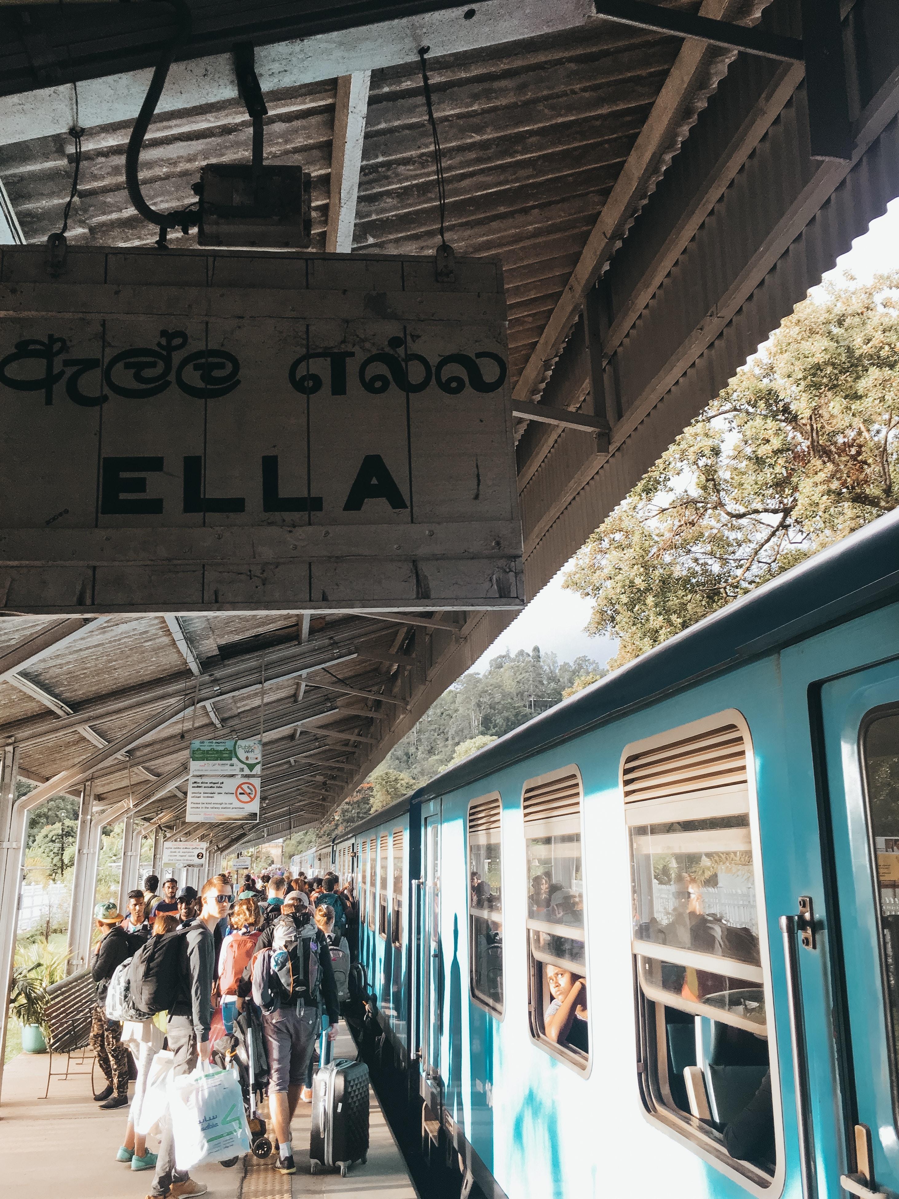 people standing beside teal train