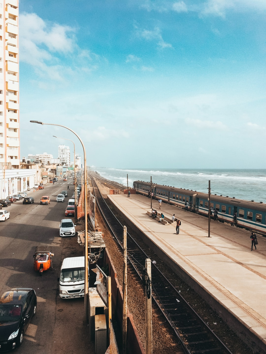 A photo of Marine Drive, Colombo. A train track lies between the sea and a road. Cars and a train drive by while people sit by the train tracks. The sky is light blue and the waves are calm.
