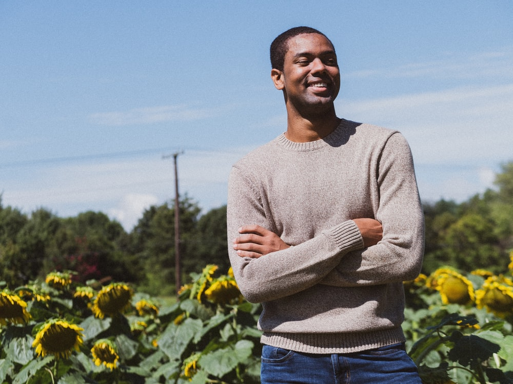 man smiling while taking photo near the sunflower
