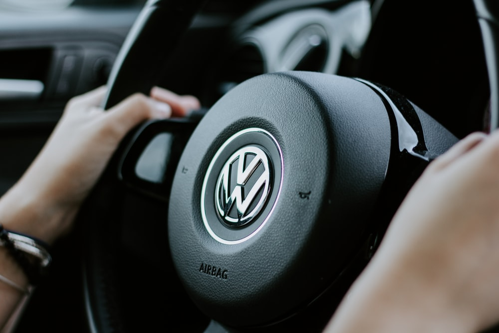 person holding black Volkswagen steering wheel in closed-up photo