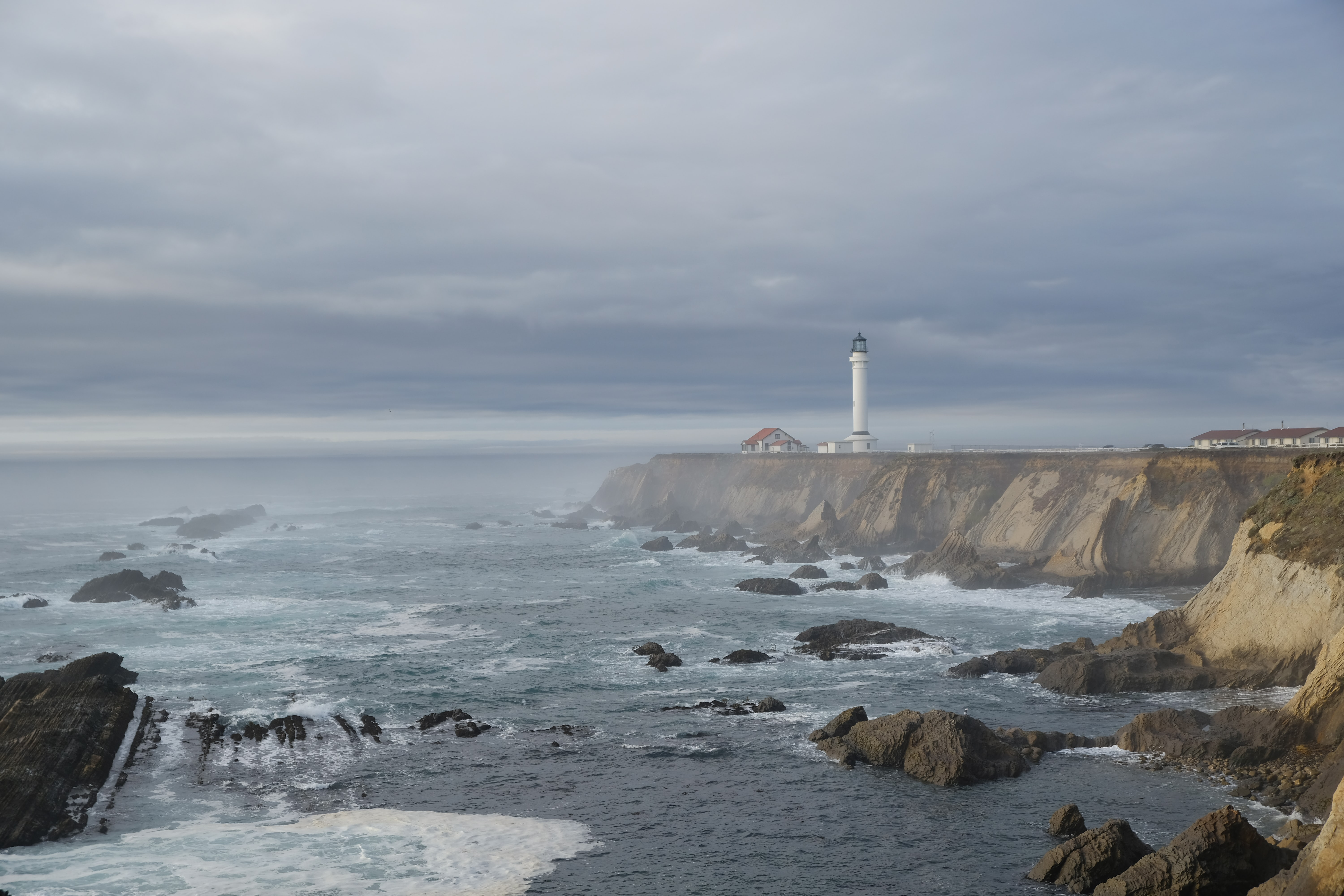 white lighthouse on shore under gray clouds at daytime