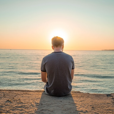 man sitting on sand front of sea during golden hour
