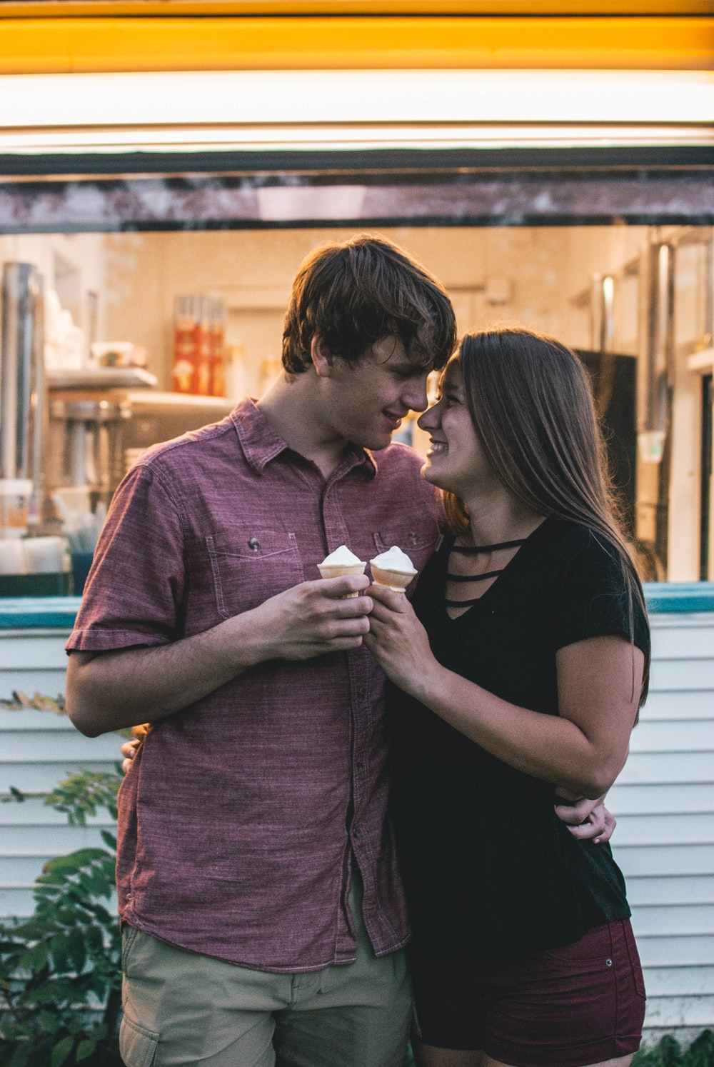 man hugging woman while holding ice cream