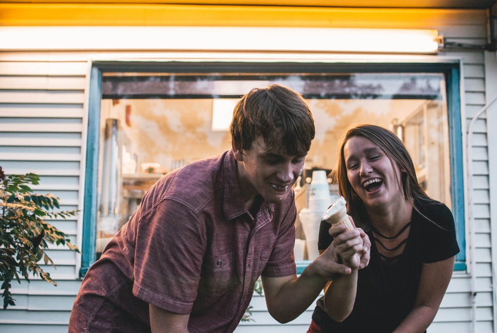 man and woman eating ice cream during daytime