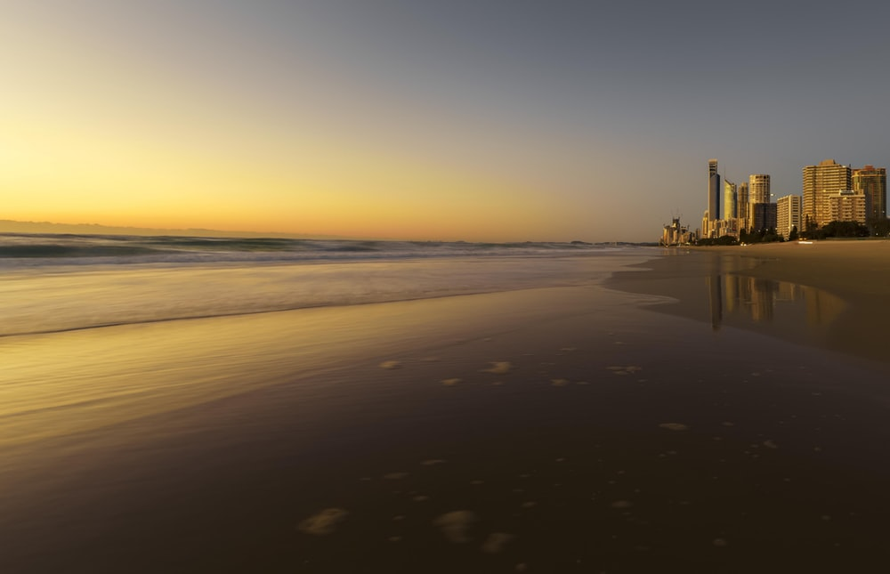 high-rise building beside seashore during golden hour