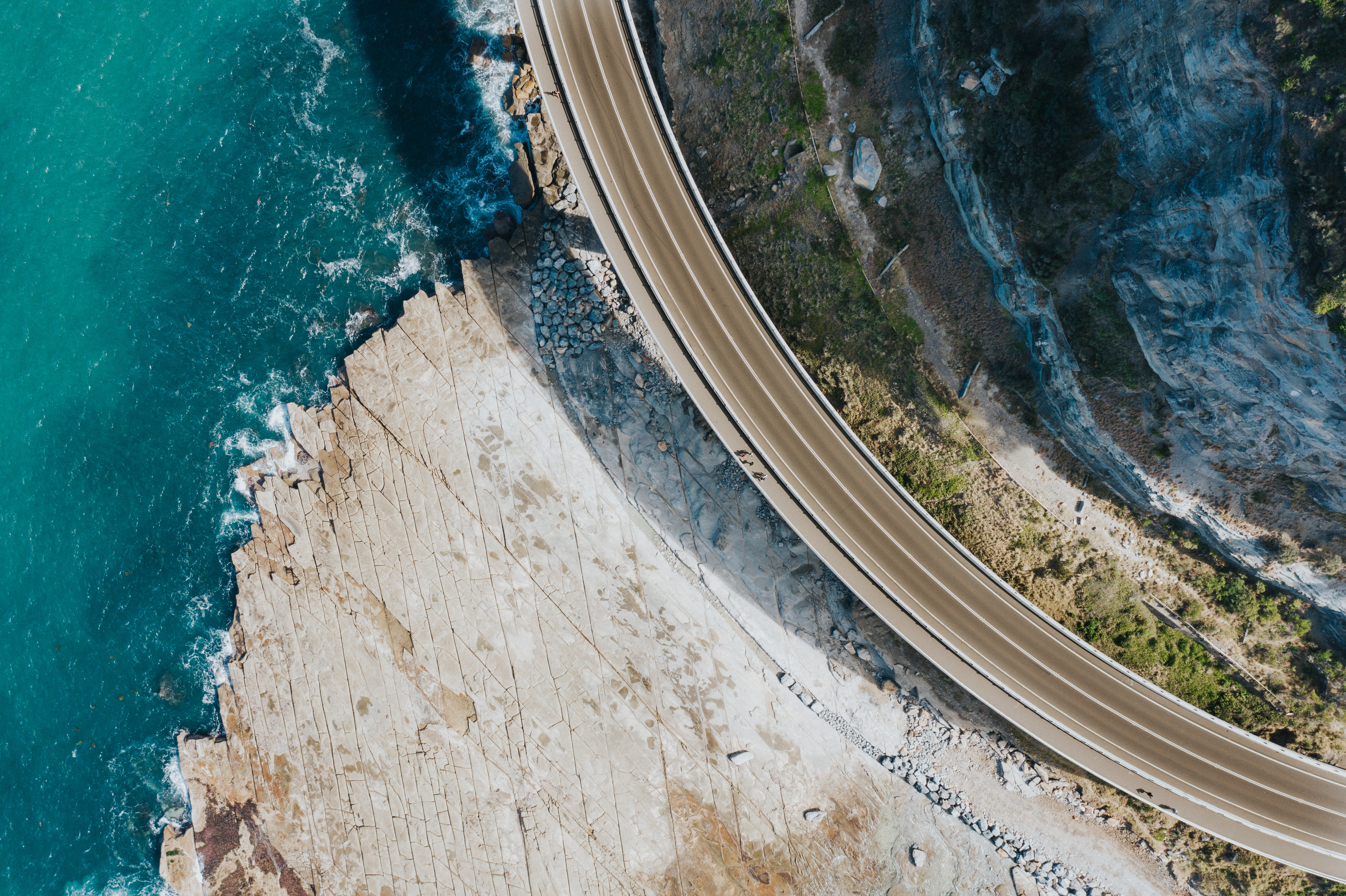 aerial view of road beside body of water