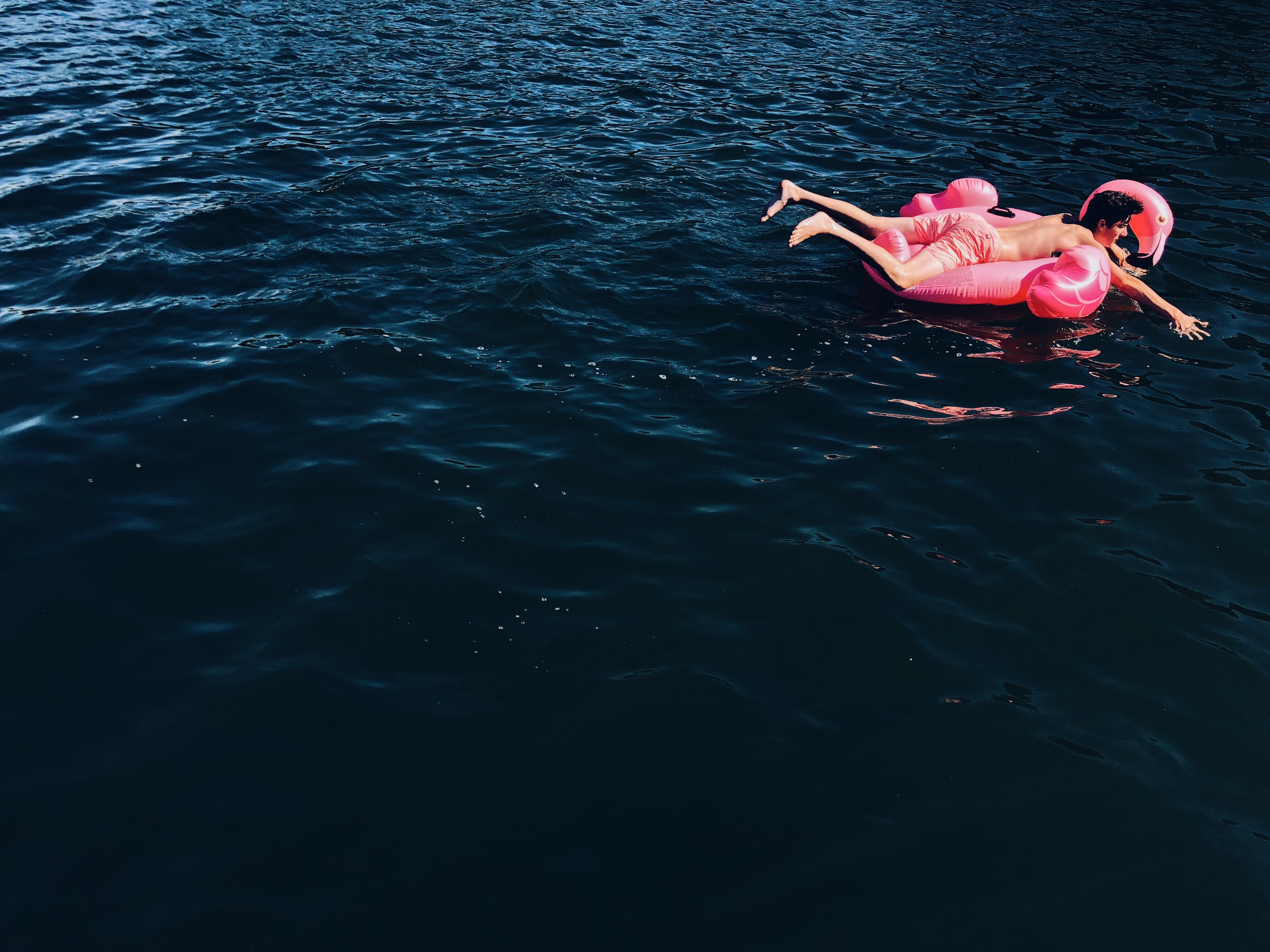 person on pink floater floating on sea