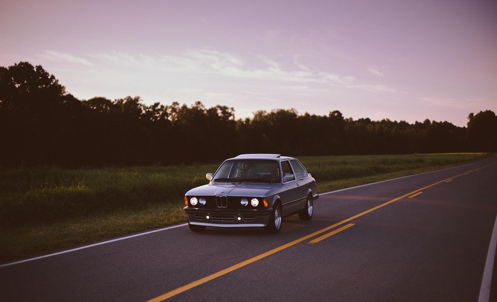 black sedan traveling on road