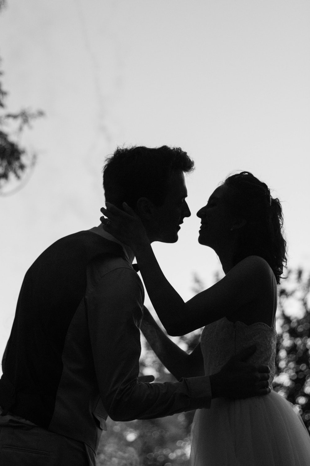 Silhouette grayscale photo of man and woman attempting to kiss