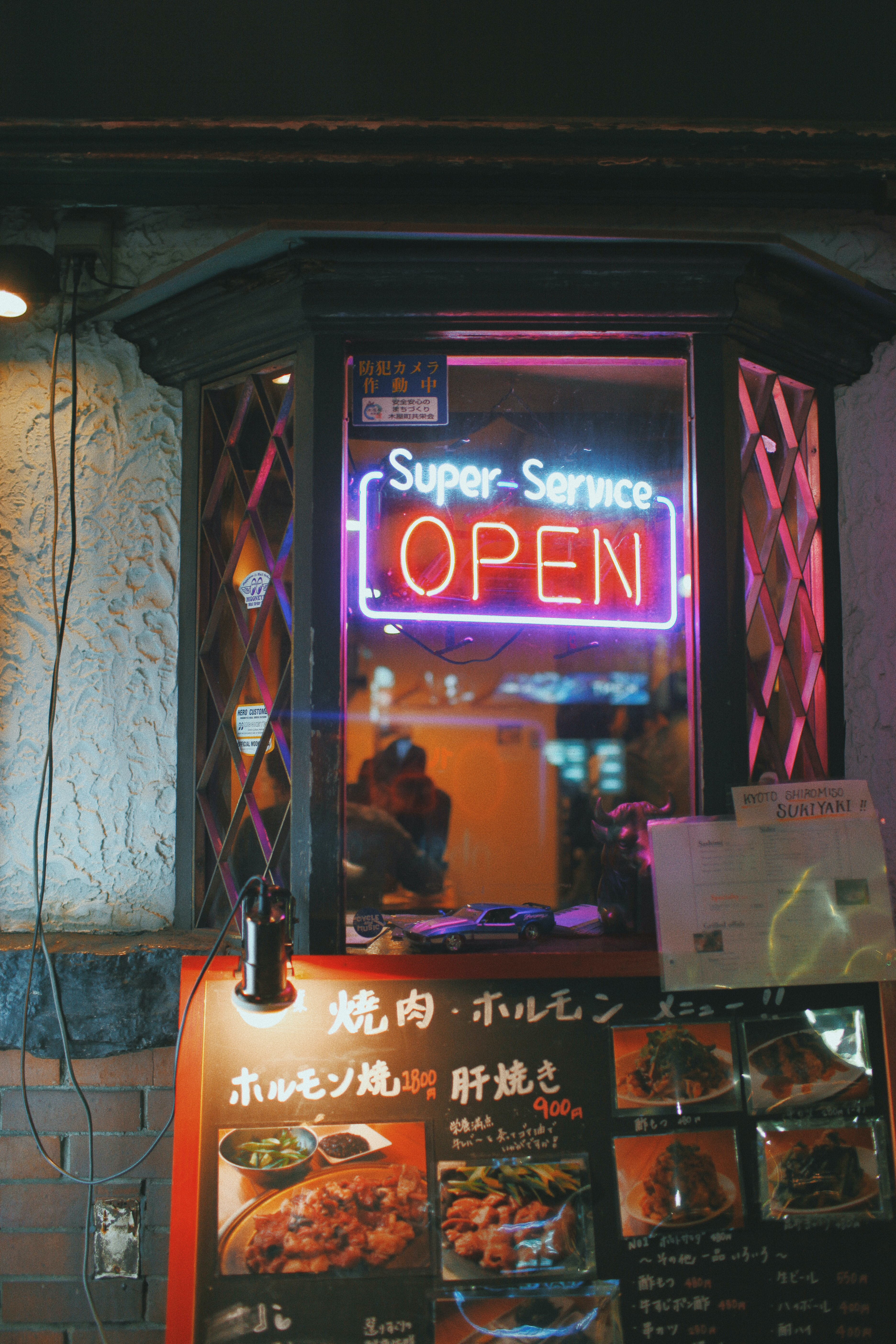 Super-Service open neon signage hanged on window