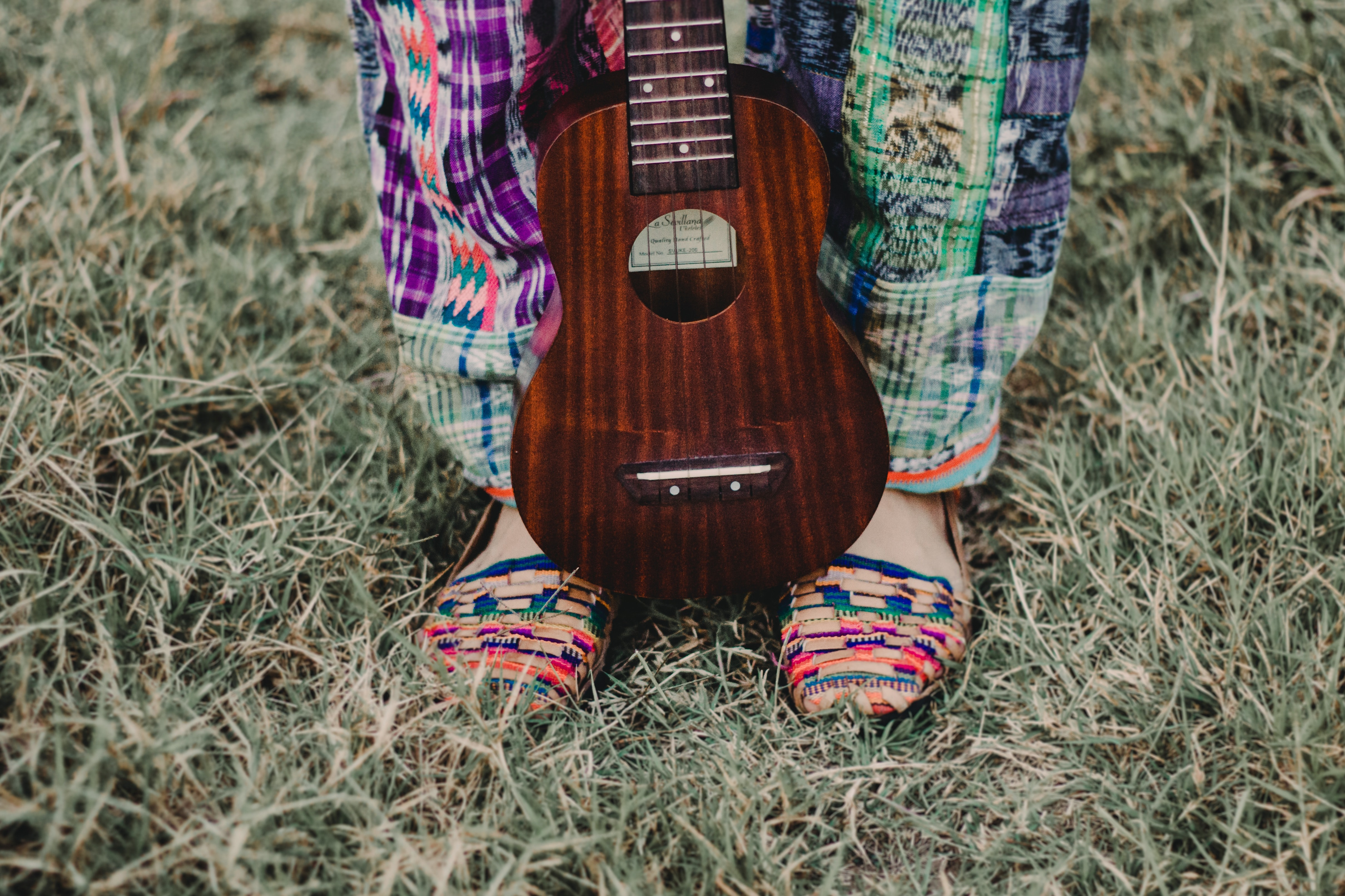 brown ukulele on person's feet