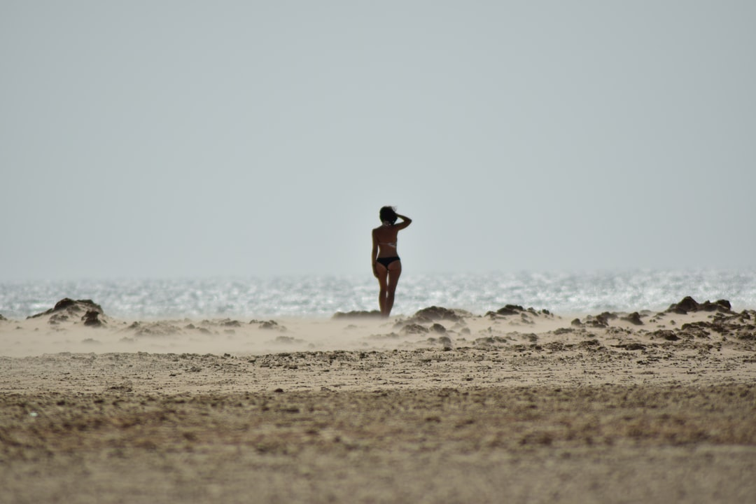 A day on the windy beach of Tarifa, Spain. A woman by the sea, looking at the horizion.