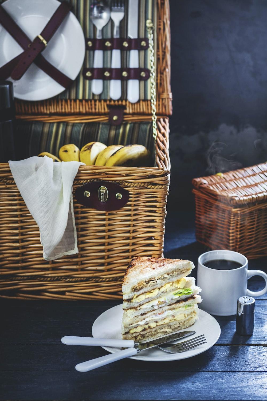 sandwich on plate beside brown wicker basket