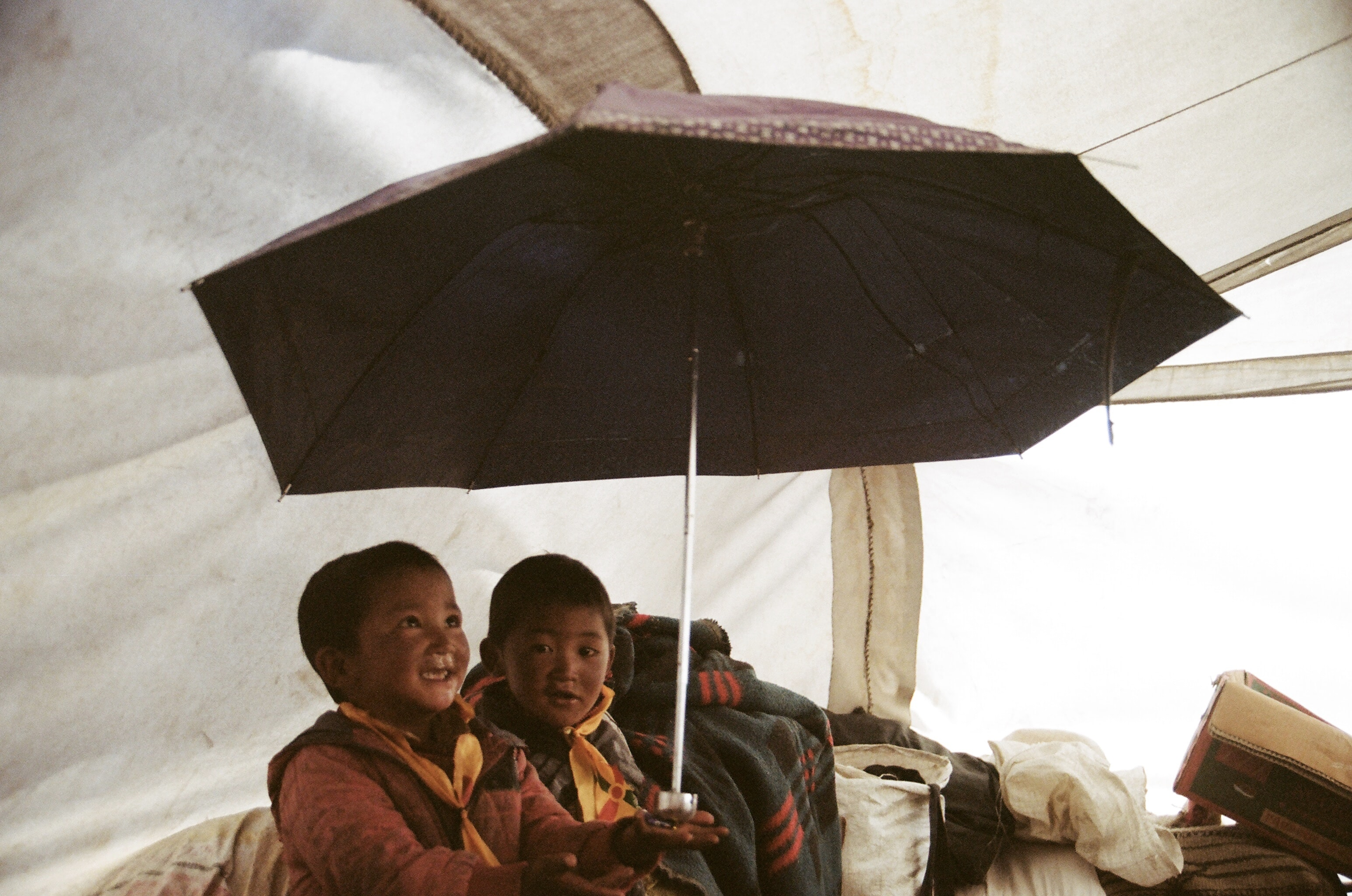 boy holding umbrella in tent