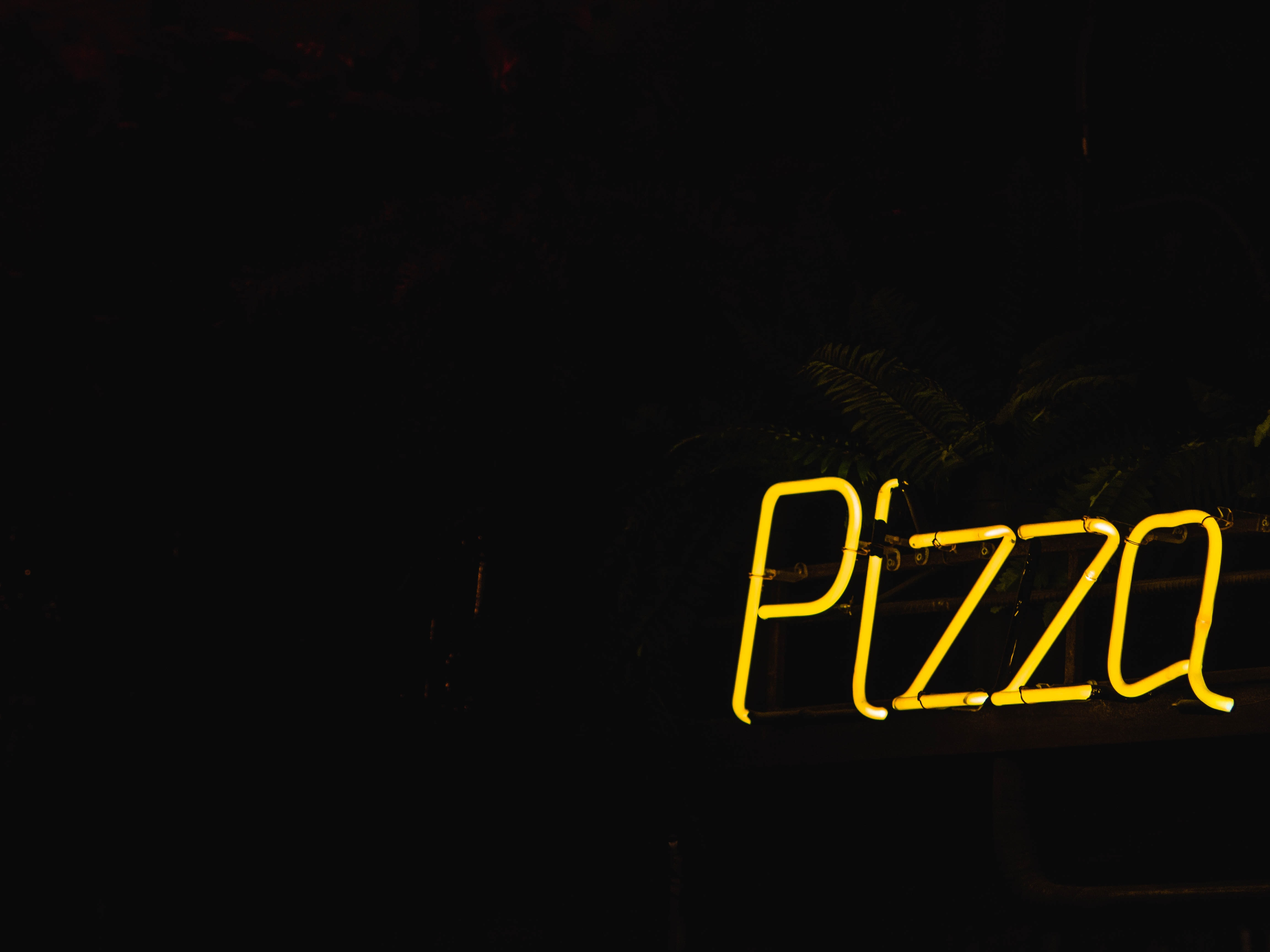 switched on yellow Pizza neon signage