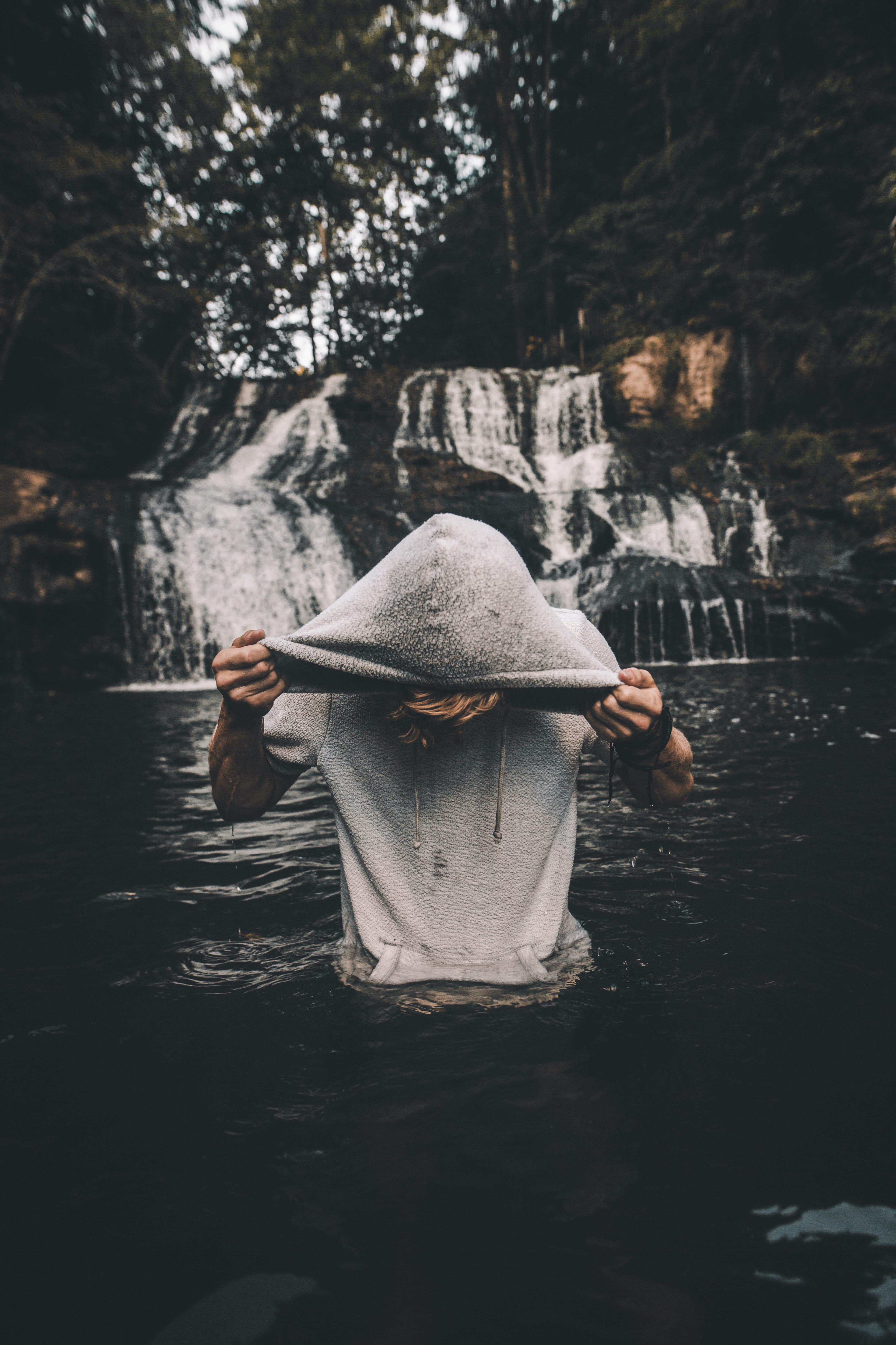 man in gray pullover hoodie in body of water