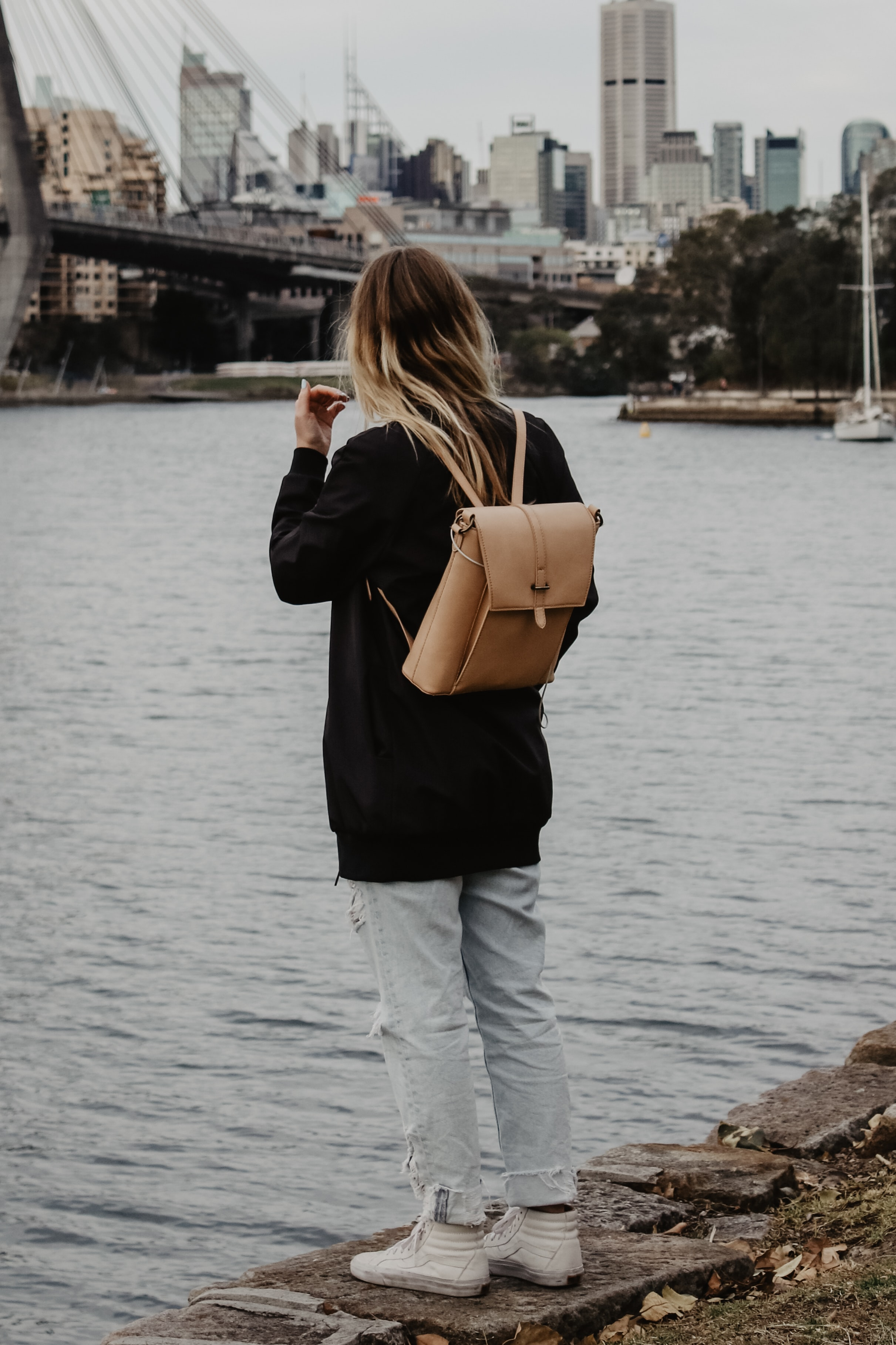 women's black jacket and brown leather bucket backpack