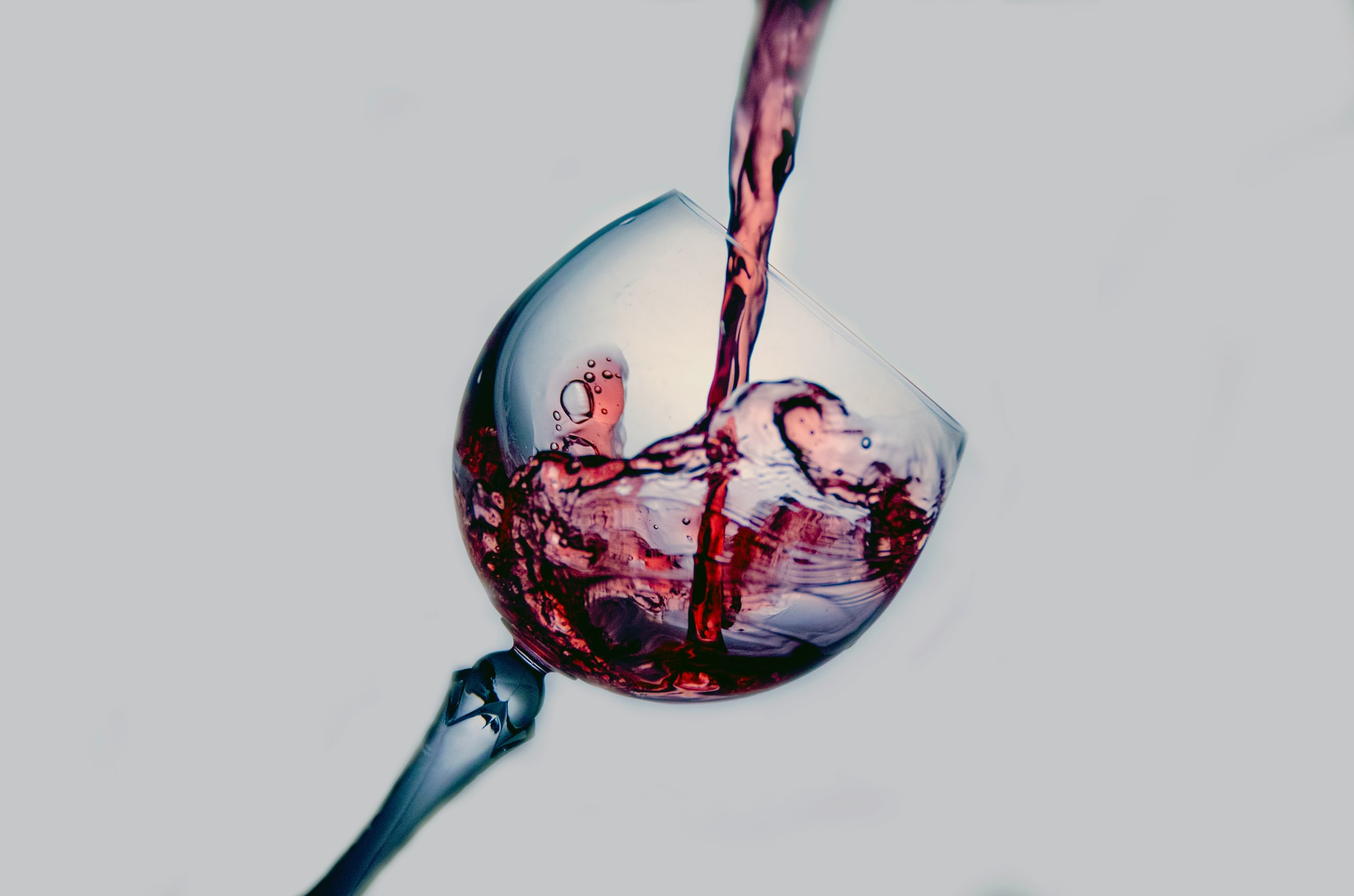 "A tilted wine glass having red nectar poured into. Have you ever thought: ""When is the best moment in anything ? "". Is it not that the best moment of your vacation is when you lock the front door of your house and turn your back to it ? Every subsequent moment just brings you closer to the end of the vacation. Drinking wine is no different. Pouring wine in the glass is the peek moment of the ceremony. After that, every drop you drink degrades your glass to an emptier one. That is of course until you fill it up again. But then is it not that you just get a new peek moment of a new ceremony ?."
