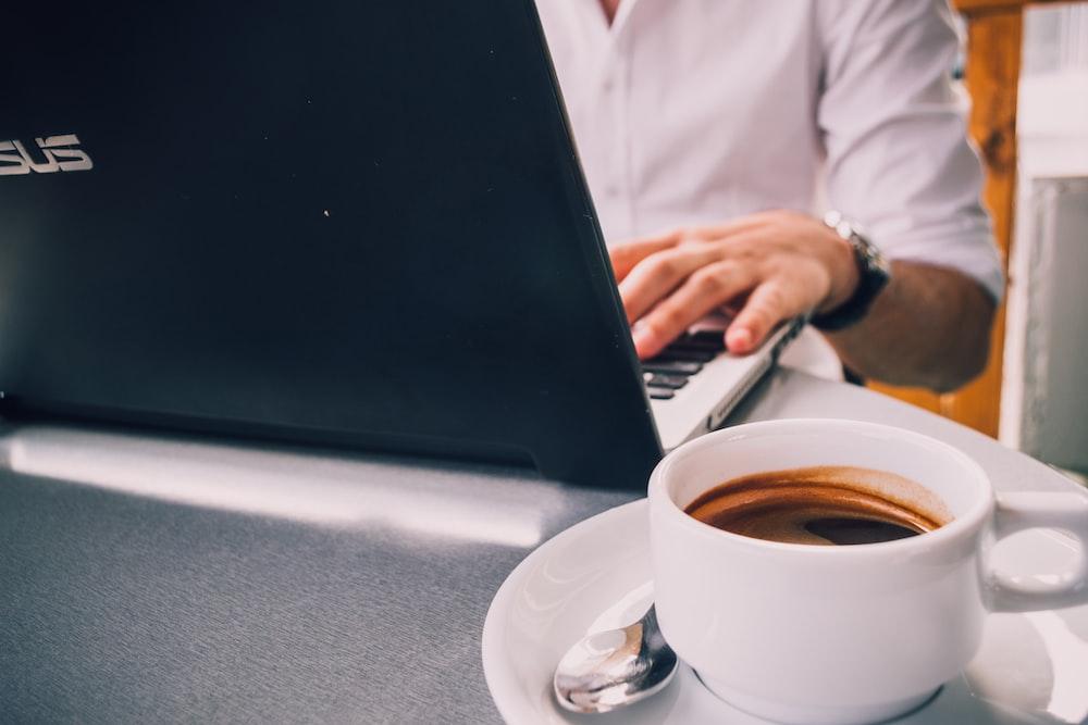 laptop beside mug on table