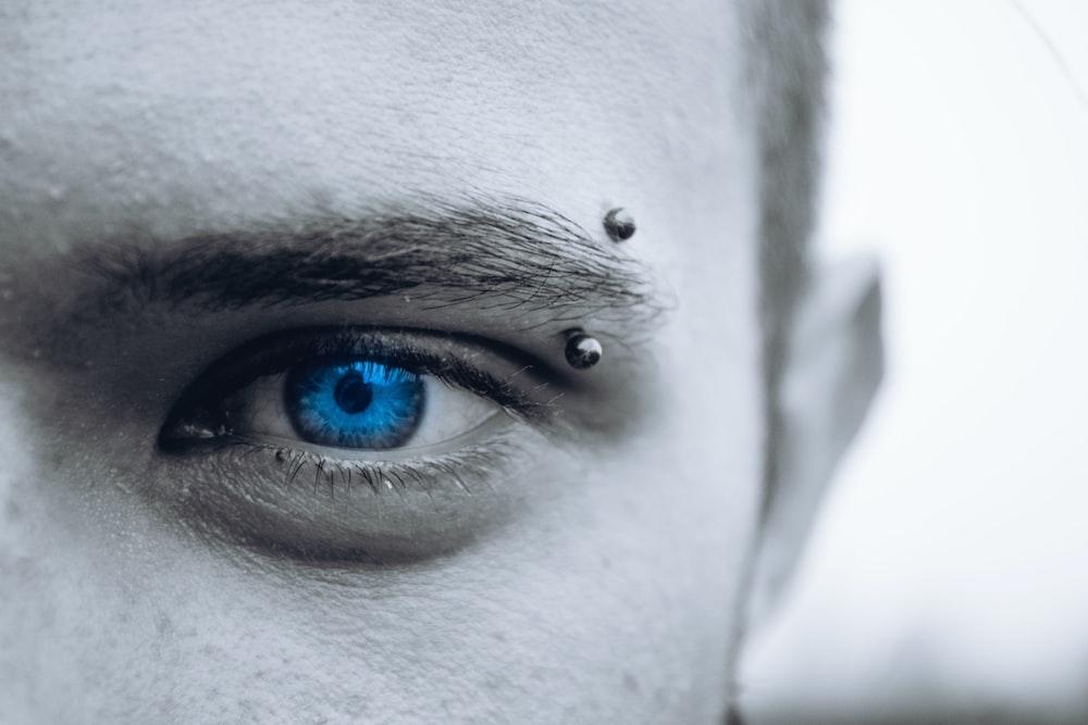 selective photo of man's blue eye